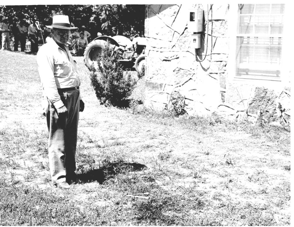 June 1951- Sheriff Ralph Willcutt points to the scene where County Attorney Jack Burris was gunned down at his Locust Grove Home.  The shotgun slaying Jack Burris remains unsolved and is one of the most famous murder investigations in the history of the State of Oklahoma.   Burris served as the elected County Attorney from 1947 until his death and is buried in Pryor's Fairview Cemetery.
