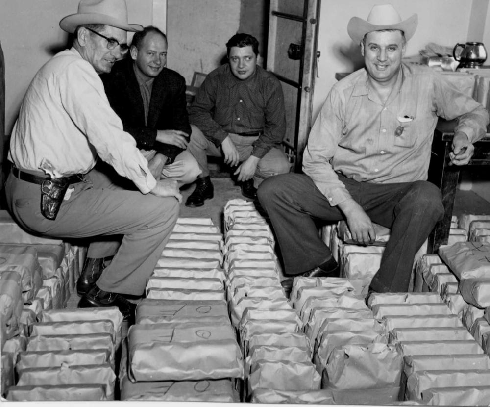 March 1956-County law officers pose with confiscated liquor; from left to right are Deputy Sheriff Fred Grimes, County Judge Carl Longmire, County Attorney Bill Thomas and Sheriff Slim Weaver.