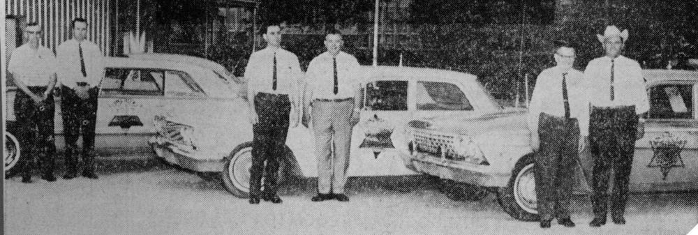 May 1965: Mayes County Sheriff Joe Faircloth and deputies posing with cars showing new Sheriff decal logo; Left to right: Lefty Poe, Harold Page, Leroy Hatfield, Joe Faircloth, Frank Nicodemus and Bob Rainwater. Faircloth was sheriff from 1965-1969.