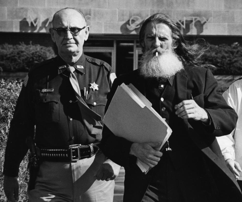 "About 1978-Undersheriff Al Boyer escorts ""Father John"" La'Aquarious back to jail from a court hearing. Father John, one of the most colorful characters in Mayes County Criminal history claimed to be the high priest of a religious cult using marijuana as part of their worship services.   He one sued Sheriff Pete Weaver for not providing daily clean bed linens service to him while in the county jail."